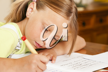 Girl preparing her homework for school writing in her exercise book