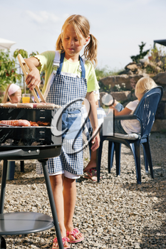 Family having a barbecue party - little kid at the barbecue grill preparing meat and sausages