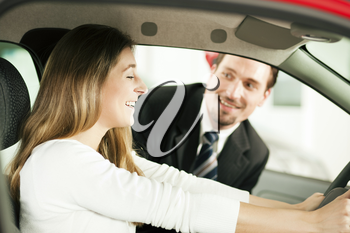 Woman buying a car in dealership sitting in her new auto, the salesman talking to her in the background