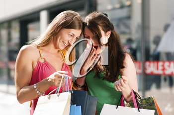 Two women being friends shopping downtown with colorful shopping bags, in the background a store can be seen with the words 'sale' in the window