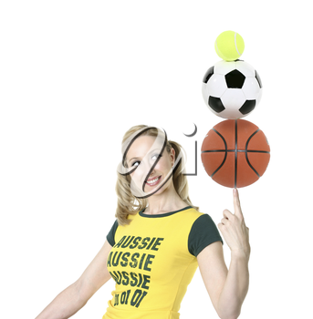 Cheerful, Aussie athletic girl in green and gold t-shirt balancing sporting balls. White background.