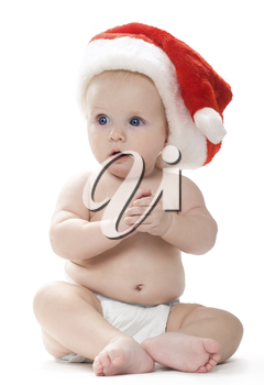 Sitting small baby in Santa cap looking aside with great astonishment