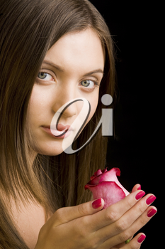 Portrait of beautiful brunette with rosebud in hands looking at camera