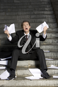 Image of grieving businessman crying with papers in hands