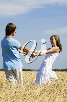 Portrait of cheerful girl and guy holding each other by hands and looking at one another