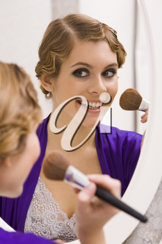 Image of pretty female looking in mirror and doing makeup