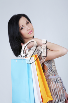 Portrait of brunette woman holding colorful bags in hand and smiling at camera