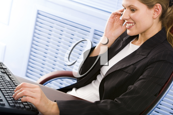 Business woman typing on the keyboard and calling on the mobile