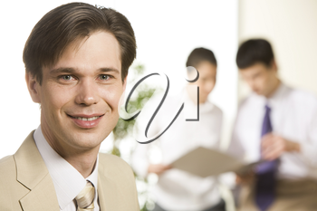 Portrait of confident businessman looking at camera on the background of coworkers