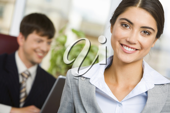Portrait of smiling businesswoman on background of her working colleague