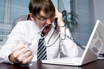 Image of aggressive boss yelling into telephone receiver to one of his employees
