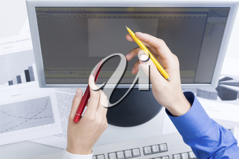Photo of male and female hands with pens by the monitor during discussion