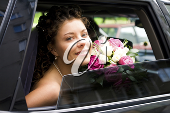 Photo of happy bride looking out of car window with bouquet in her hands