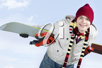 Photo of skillful teenager with snowboard behind his back over blue background