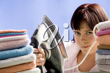 Portrait of young female between two stacks of colorful towels looking to camera