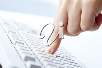 Image of human forefinger on keyboard button