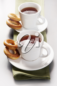 Row of cups of tea with bread-rings near by