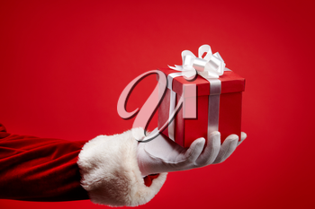 An image of Santa�s hand holding a gift box against red background