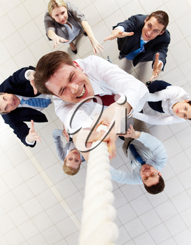Above view of happy employer ascending up the rope with several employees beneath