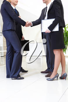 Image of business people handshaking after signing agreement