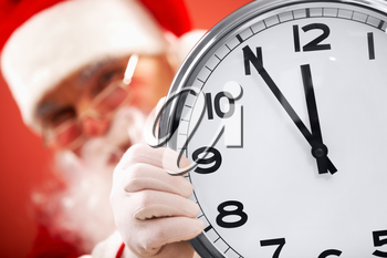 Photo of clock showing five minutes to midnight with Santa on background