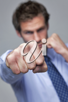 Businessman throwing a punch towards the camera, focus on his fist.