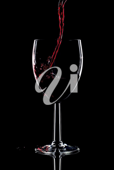 Red wine being poured into a glass and splashing over the side. Low key black background.