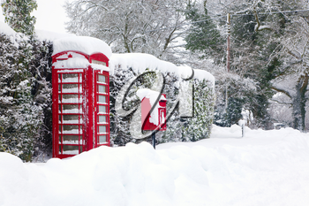 A red British telephone and post box in the snow.
