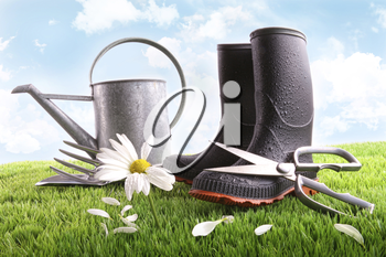 Royalty Free Photo of Rubber Boots, Sheers and a Watering Can on the Grass