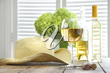 Royalty Free Clipart Image of a Bottle and Glass of Wine on a Table With a Plant and Straw Hat