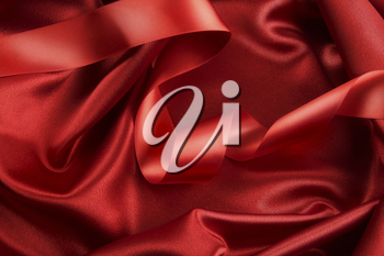 Royalty Free Photo of a Red Ribbon Lying on Red Satin
