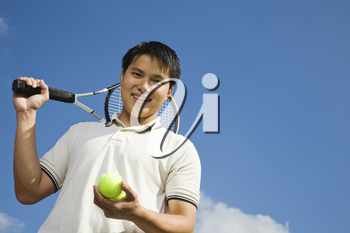 A happy sporty asian male playing tennis