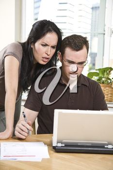 A stressed couple paying bills by using online banking at home