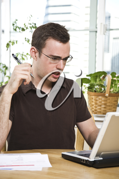 A confused caucasian man paying the bills by online banking at home