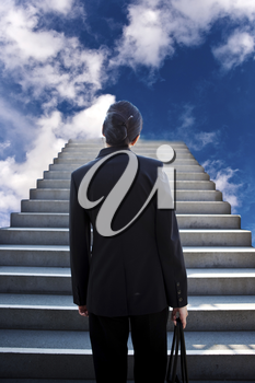 A conceptual shot of a businesswoman at the bottom of the stairs