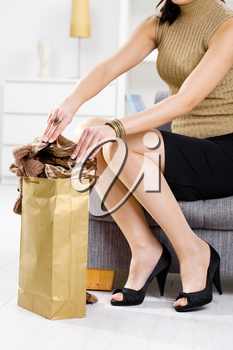 Elegant young woman sitting on couch, packing out from shopping bag.