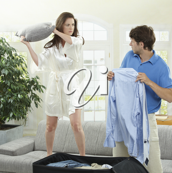 Unhappy couple fighting. Woman hitting man who is  packing his clothes with a pillow.