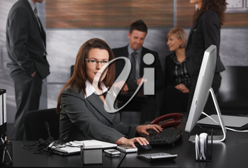 Mid-adult businesswoman dealing with computer tasks sitting at desk in office, looking at camera.