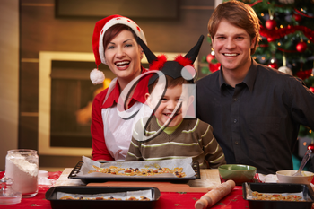 Christmas portrait of happy family of three, looking at camera, smiling.