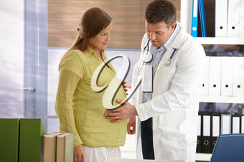 Doctor touching pregnant woman's belly in consuting room.
