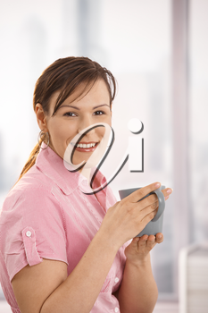 Portrait of happy office worker holding tea cup, looking at camera, smiling.