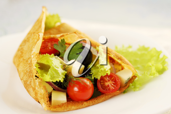 Pancake stuffed with salad, cheese, tomatoes and olives