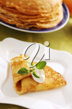 Pancake with sour cream on the plate