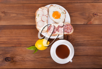 Sandwiches and tea on a wooden background. View from above .