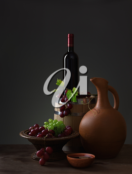 Bottle of red wine, pitcher, grapes and wooden barrel