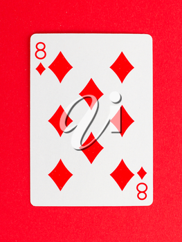 Old playing card (eight) isolated on a red background