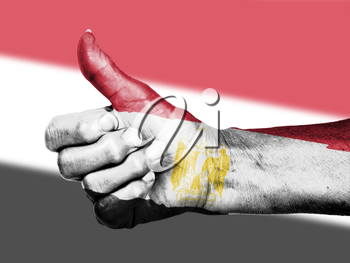 Old woman with arthritis giving the thumbs up sign, wrapped in flag pattern, Egypt