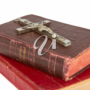 Old antique bible and cross on a white background, isolated