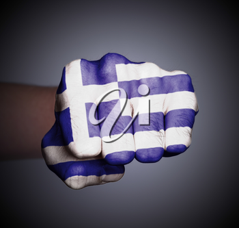 Front view of punching fist on gray background, flag of Greece