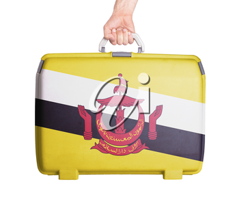 Used plastic suitcase with stains and scratches, printed with flag, Brunei